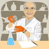 Senior male scientist mixing chemicals in laboratory. Senior male scientist with glasses mixing chemicals in laboratory Stock Image