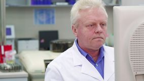 Male scientist watches some process at the laboratory. Senior male scientist watching some process at the laboratory. Caucasian man in white coat turning his Stock Photos