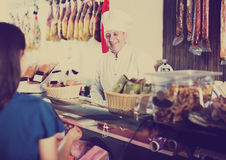 Senior male seller with wursts and female purchaser Stock Image