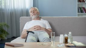 Senior male sleeping on sofa at home, relax after taking pills, medication. Stock footage Stock Photo