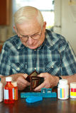 Senior male spent money on medicine. A senior citizen holds his open wallet signifying the high cost of prescription medications. He is surrounded by pill Royalty Free Stock Images