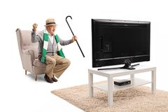 Senior male sports fan with a cane and a scarf sitting in an armchair watching a game on tv and cheering royalty free stock photography