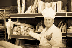 Senior male staff offering fresh baguettes and buns. In bakery Royalty Free Stock Images