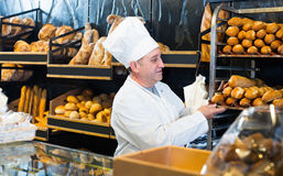 Senior male staff working with fresh baguettes and buns. In bakery Royalty Free Stock Photography