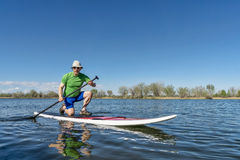 Senior male on stand up paddleboard. Senior male exercising on stand up paddling (SUP) board. Early spring on a calm lake in Fort Collins, Colorado Royalty Free Stock Photography