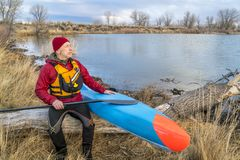 Senior male with stand up paddleboard. Senior male paddler is resting on a lake shore after workout on his racing stand up paddleboard, early spring Colorado Royalty Free Stock Images