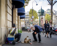 Senior male stops to chat with two cats on Paris street Stock Images