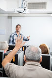 Senior Male Student Raising Hand In Computer Class. Senior male student raising hand while tutor explaining in computer class Royalty Free Stock Photo