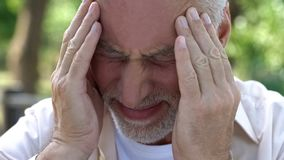 Senior male suffering strong headache, touching temples, high pressure problem. Stock photo royalty free stock photography