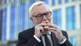Senior male in suit eating burger during lunchtime, standing near office center. Senior male in suit eating burger during lunch, standing near office center stock photo