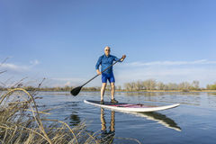 Senior male on SUP paddleboard Stock Photos
