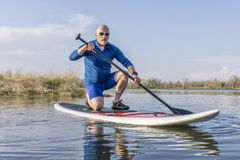 Senior male on SUP paddleboard Stock Photography