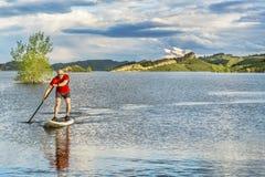 Senior male SUP paddler on lake Stock Photos