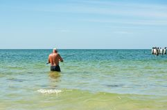 Senior male surf fishing. In the calm waters of the Gulf of Mexico with pilings and bird off shore Stock Images