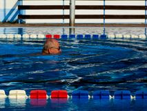 Senior male swimmer in outdoors open pool in blue water royalty free stock image