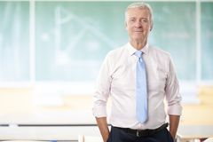 Senior math professor. A senior male teacher standing in front of the blackboard after math lesson Stock Image