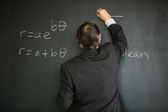 Senior male teacher teaching mathematics. Writing on the blackboard Royalty Free Stock Photos