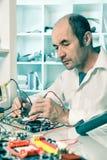 Senior male tech fixes epectronics. Senior male tech tests electronic equipment Royalty Free Stock Image