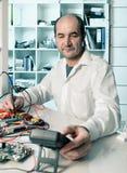 Senior male tech fixes epectronics. Senior male tech tests electronic equipment Royalty Free Stock Photo
