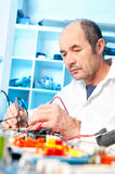 Senior male tech tests electronic equipment. In service centre Stock Images