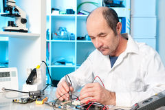 Senior male tech repairs circuit board Royalty Free Stock Photography