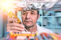 Senior male tech tests electronic equipment Stock Photos