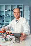 Senior male tech tests electronic equipment. This image is toned Stock Photos