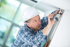 Senior male technician installing camera on wall. Cctv Royalty Free Stock Photography