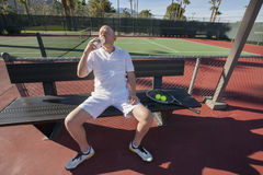 Senior male tennis player drinking water while relaxing on court Stock Photos