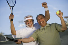 Senior Male Tennis Player Enjoying Success. Excited senior male tennis player enjoying success while playing doubles Royalty Free Stock Photography