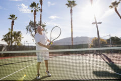 Senior male tennis player holding racket on court Royalty Free Stock Photography