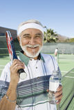 Senior Male Tennis Player Holding Water Bottle. Portrait of a happy senior male tennis player holding water bottle at court Stock Image
