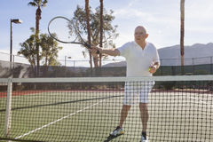 Senior male tennis player preparing to serve on court Stock Photography