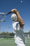 Senior Male Tennis Player Serving Stock Images