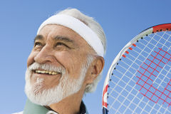 Senior Male Tennis Player Smiling. Close-up of a happy senior male tennis player looking away against sky Stock Images