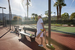 Senior male tennis player stretching leg on court Royalty Free Stock Photography