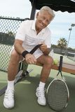 Senior Male Tennis Player Wearing Wristband. Full length portrait of a happy senior male tennis player wearing wristband Stock Photo