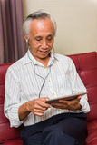 Senior male using technology for entertainment Royalty Free Stock Images