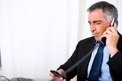 Senior male waiting on telephone. Portrait senior male waiting on telephone at the office Royalty Free Stock Image
