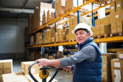 Senior male warehouse worker or a supervisor pulling a pallet truck with boxes. Senior male warehouse worker or a supervisor with white helmet pulling a pallet Stock Photography