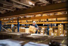 Senior male warehouse worker or a supervisor unloading a pallet truck with boxes. Senior male warehouse worker or a supervisor with white helmet loading or Stock Images