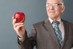 Senior man teacher wearing glasses studio standing on gray looking at apple thinking joyful close-up blurred. Senior male wearing eyeglasses teacher studio stock images