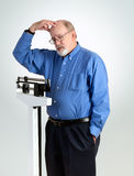 Senior Male on Weight Scale. Senior caucasian man weighing himself on vertical weight scale. He is rubbing his forehead and looks worried and slightly confused Stock Photo