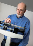Senior Male on Weight Scale Closeup. Senior caucasian man weighing himself on vertical weight scale. He looks thoughtful and concerned royalty free stock images