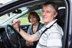 Senior male and woman sitting in car and smiling Stock Images