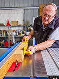 Senior male woodworker using a saw bench. Senior male woodworker guiding a piece of wood through a saw bench machine in a workshop Royalty Free Stock Photography