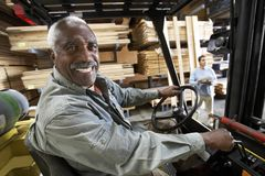 Senior Male Worker Driving Forktruck. Portrait of a happy senior male worker driving forktruck Royalty Free Stock Photos
