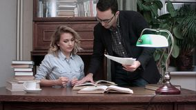 Senior male worker in glasses holding report and explaining tasks to female coworker sitting at the table stock image