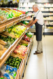 Senior male worker stocking the vegetables. In supermarket Royalty Free Stock Photos