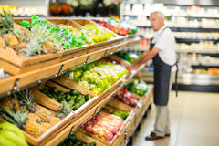 Senior male worker stocking the vegetables. In supermarket Stock Photography